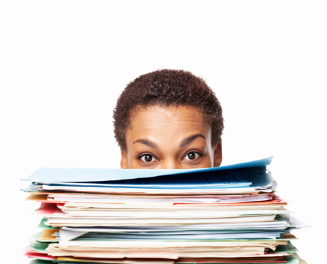 African American Woman Looking Over Work Files - Isolated